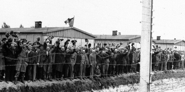 Prisoners at the electric fence of Dachau concentration camp cheer the Americans in Dachau, Germany in...