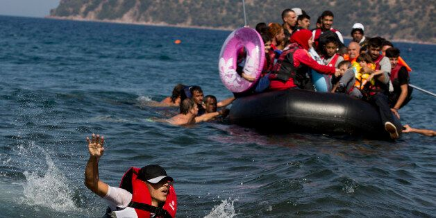 A Syrian man swims in front of a dinghy full of refugees that suffered engine failure as they approached...