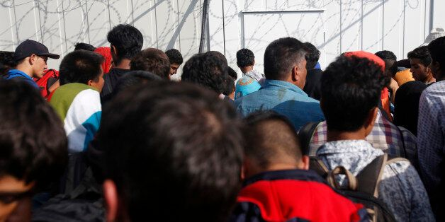 Migrants wait in front of the container on no man's land at the Horgos border crossing into the Hungary,...