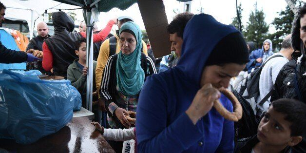 Refugees and migrants queue as police officers hand out milk and bread in the northern Greek village...