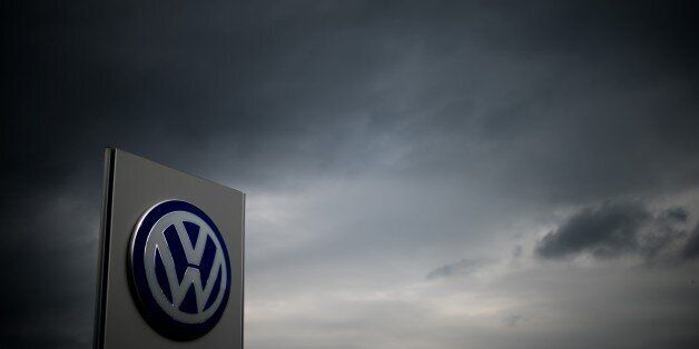 The logo of German car maker Volkswagen can be seen as dark clouds hang in the sky over a Volkswagen...