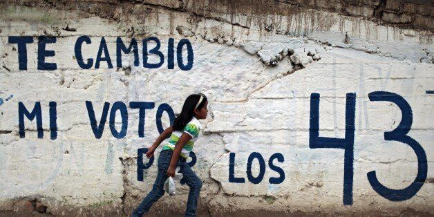 A girl passes by a wall with a graffiti calling to boycot upcoming elections and asking for the 43 missing...