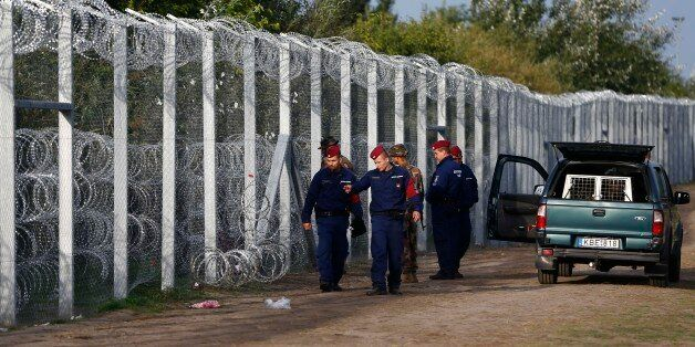 Hungarian police officers check a hole at the fence where migrants tried to cross the border line between...