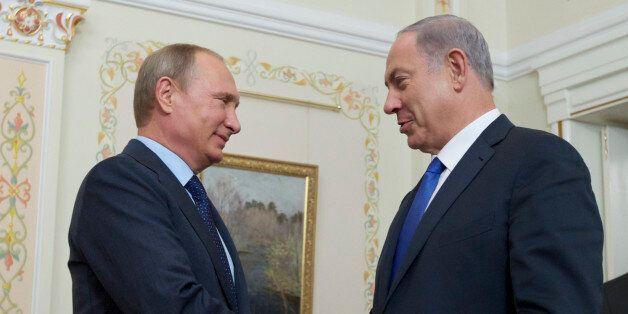 Russian President Vladimir Putin shakes hands with Israeli Prime Minister Benjamin Netanyahu, right,...