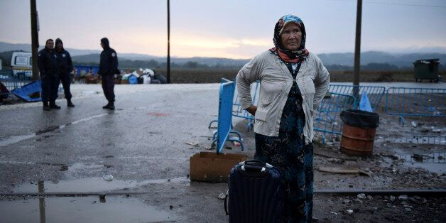 A woman waits with her bags to cross the border from the northern Greek village of Idomeni to southern...
