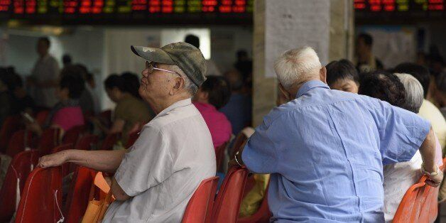 Investors monitor screens showing stock market movements at a brokerage house in Shanghai on July 29,...
