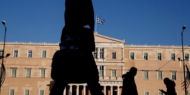 Pedestrian walks past the Greek parliament in central Athens, on Wednesday, Jan. 7, 2015. Greeks go to...