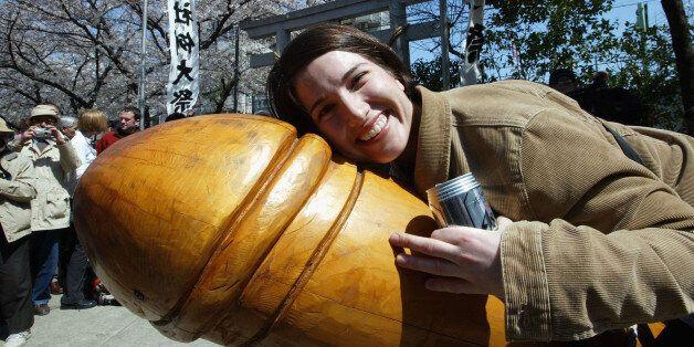 KAWASAKI, JAPAN - APRIL 6: An unidentified woman nestles up to a huge wooden penis April 6, 2003 in Kawasaki,...