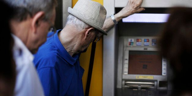 Pensioners and customers wait to withdraw cash from an automated teller machine (ATM) outside a Piraeus...