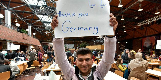 A refugee from Afghanistan holds a banner reading 'Thank you Germany' at a hall in Dortmund, Germany,...