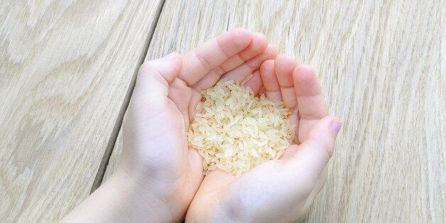hand of the boy raised a handful of rice on wood