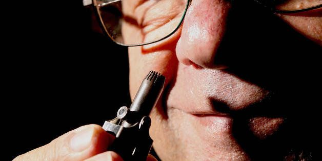 Author Maurice Collins demonstrates a mechanical nasal hair trimmer at the opening of the exhibition...