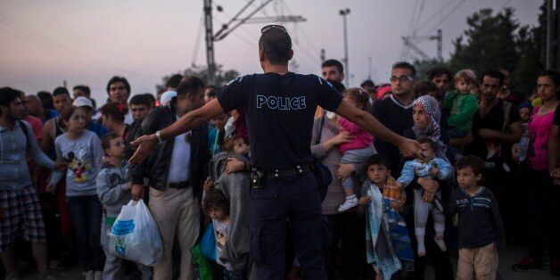 A Greek police officer gives orders to Syrian refugees as they wait to cross the border from Greece to...