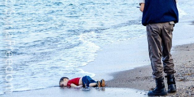 GRAPHIC CONTENTA Turkish police officer stands next to a migrant child's dead body off the shores in...