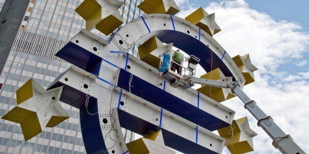 A man works on the statue of the Euro logo in front of the former headquarters of the European Central...