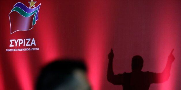 Syriza's leader, former prime minister Alexis Tsipras is silhouetted on a stage as a security stands...