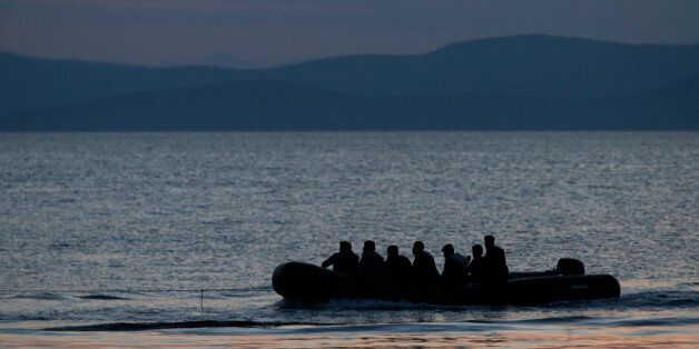 A dinghy with Syrian migrants is towed by a Greek coast guard patrol boat into the port of Kos, Greece,...