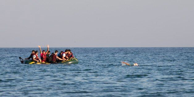 Migrants and refugees, one of them swims, arrive after crossing from Turkey, at the southeastern island...