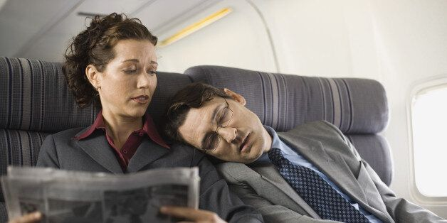 Passengers sleeping and reading on airplane