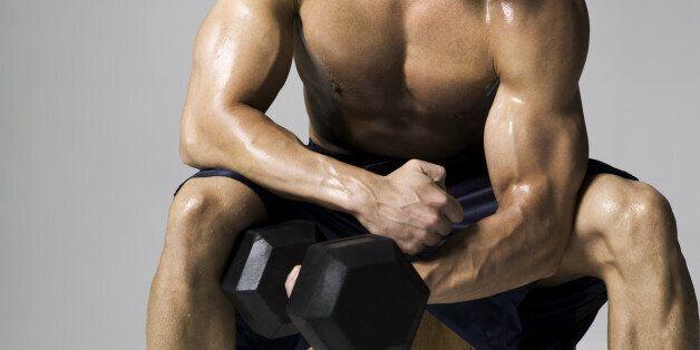 medium shot of a male bodybuilder as he lifts a weight