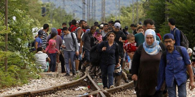 Migrants arrive at the railway station in the southern Macedonia's town of Gevgelija, after breaking...