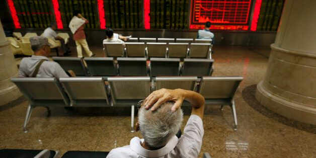 Chinese investors monitor stock prices at a brokerage house in Beijing, Monday, Aug. 24, 2015. Stocks...