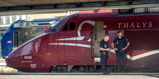 French police stand guard along the platform next to a Thalys train of French national railway operator...