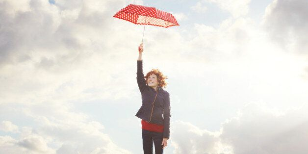 Young woman flying with umbrella.
