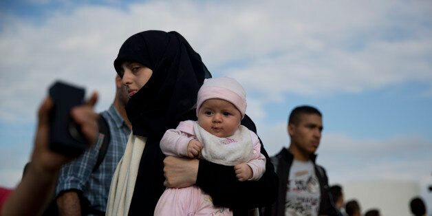 A Syrian refugee holds a baby after they arrived from eastern islands with a ferry at Athens' port of...