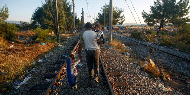 A migrant man carrying an infant in his arm takes a hand of another child as they walk on the train tracks...