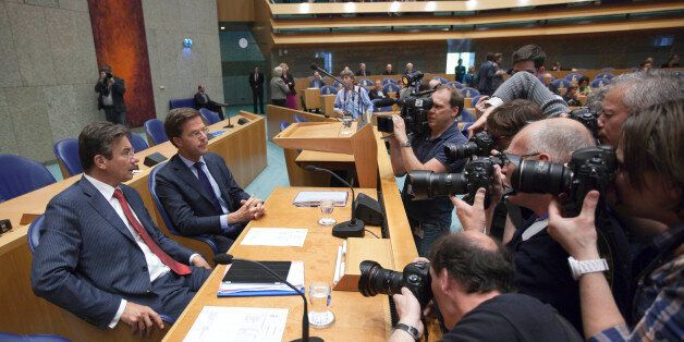 Photographers and cameramen crowd around caretaker Prime Minister Mark Rutte, second left, and deputy...