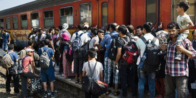 Migrants wait for a train heading to the border with Serbia at the train station of Gevgelija, on the...