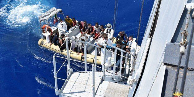 In this photo provided by the Italian Navy, migrants get aboard the Italian