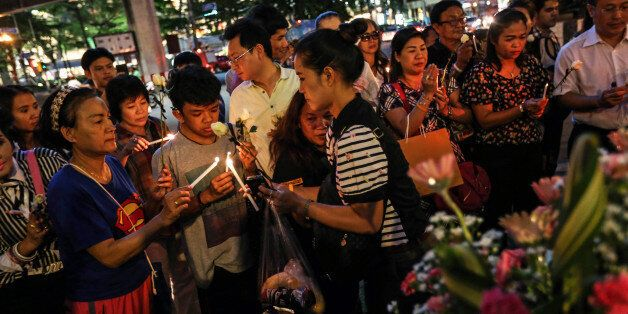 People light candles and pray for the victims of a bomb blast at the reopened Erawan shrine in Bangkok,...