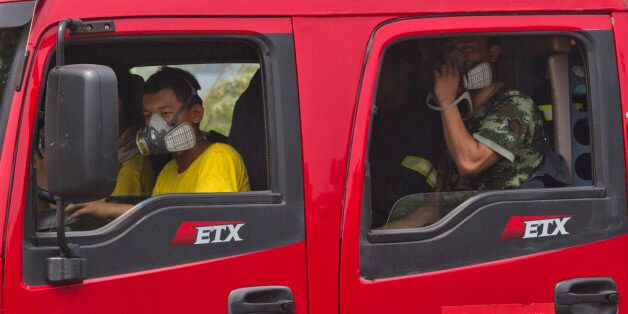 Chinese firefighters wear masks as they wait in their truck near the site of an explosion in northeastern...