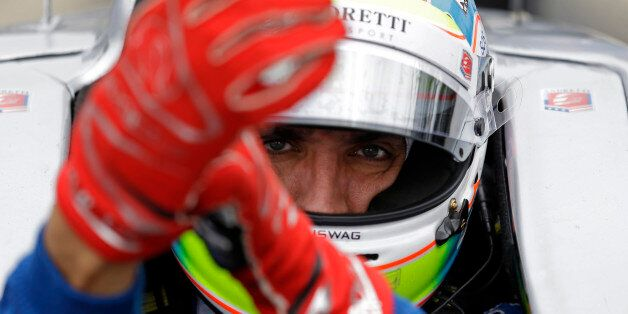 Justin Wilson, of England, dons his gloves as he prepares to drive during practice for the Indianapolis...