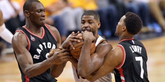 May 25, 2016; Cleveland, OH, USA; Toronto Raptors center Bismack Biyombo (8) and guard Kyle Lowry (7) battle with Cleveland Cavaliers center Tristan Thompson (13) for a loose ball during the second half in game five of the Eastern conference finals of the NBA Playoffs at Quicken Loans Arena. The Cavs won 116-78. Mandatory Credit: Ken Blaze-USA TODAY Sports
