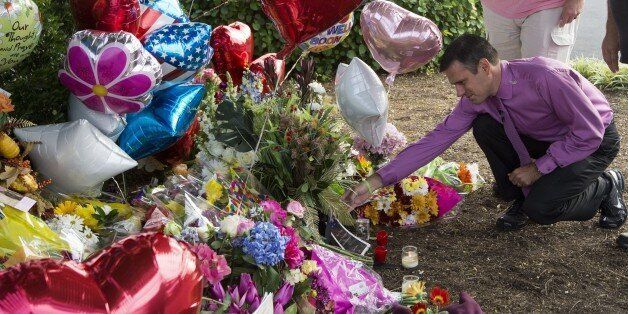 WDBJ TV weatherman Leo Hirshbrunner(C) views the makeshift memorial with members of the crew at the gate...