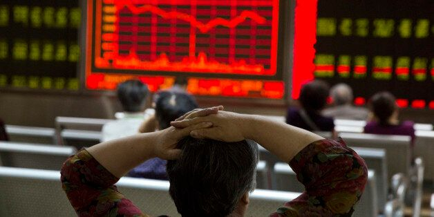 An investor watches a display of stock prices at a brokerage in Beijing, Friday, Aug. 21, 2015. Asian...