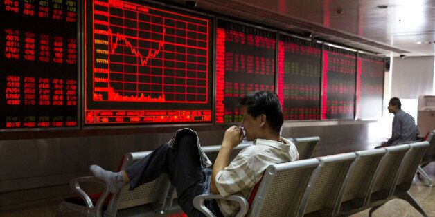 A Chinese investor monitors stock prices at a brokerage in Beijing on Wednesday, Aug. 26, 2015. Asian...