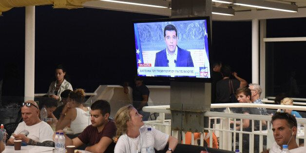 Greek Prime Minister Alexis Tsipras, on a screen during a televised address to the nation, as a tourist...