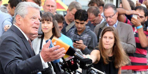 German president Joachim Gauck, left, speaks as he visits a asylum-seekers home in Berlin-Wilmersdorf...