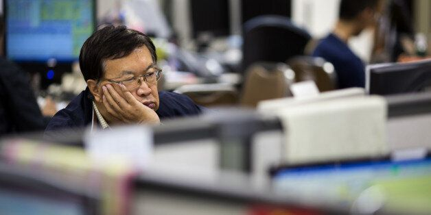 A stockbroker sits in front of a screen displaying share prices at a securities brokerage in Hong Kong,...