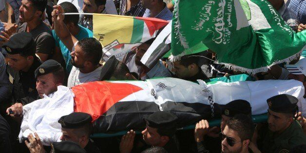 Members of the Palestinian security forces carry the body of Saad Dawabsha, the father of a Palestinian...