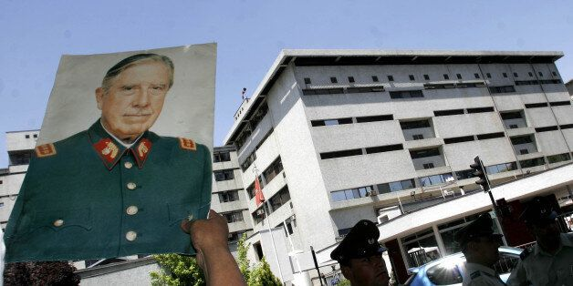 A supporter of former Gen. Augusto Pinochet raises a portrait of him in front of the Military Hospital...