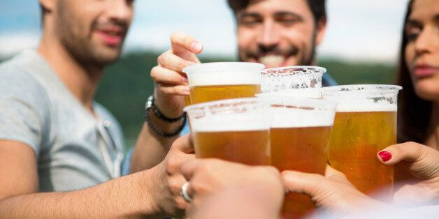 Group of friends toasting with beer in plastic
