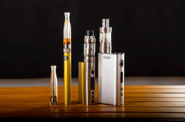 Popular vaping e cig devices mod.electronic cigarette over a wood background. vaporizer e-cig old device