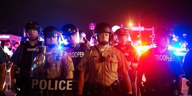 St. Louis County Police and Missouri State Highway Patrol troopers stand guard as protesters march on...