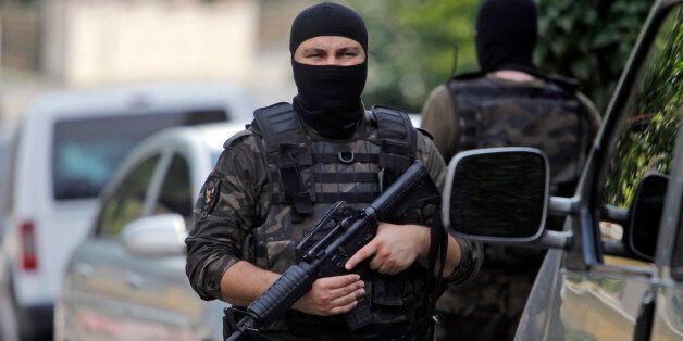 Masked Turkish police officers secure a road leading to the U.S. Consulate building in Istanbul, Monday,...