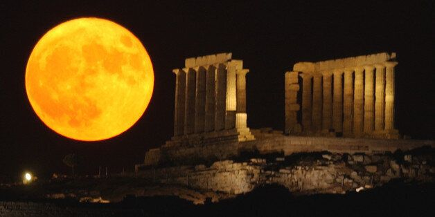 The full moon rises behind the ancient temple of Posseidon, in Sounio about 73 kilometers (45 miles)...